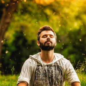 Mann meditiert in Natur