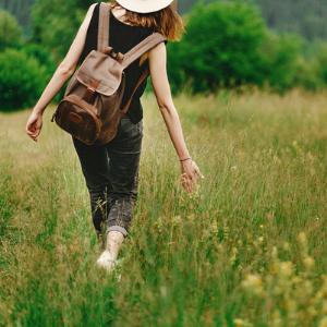 Frau spaziert auf Wiese